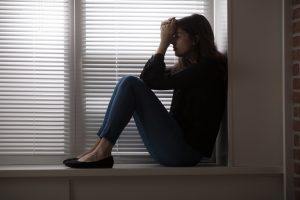 Young depressed woman sitting in a windowsill.