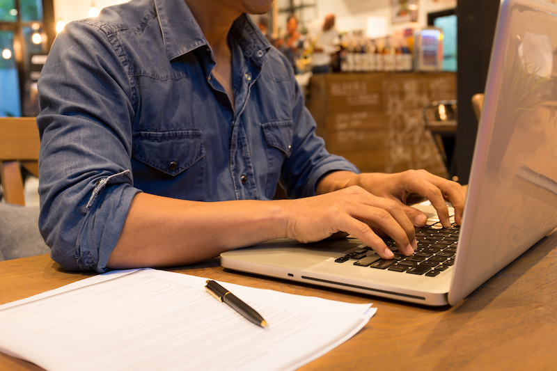 Young casual man working on laptop in cafe at night