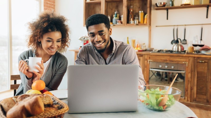 Remote work and freelance. Affectionate black woman looking at her boyfriend working on laptop in kitchen, panorama, copy space