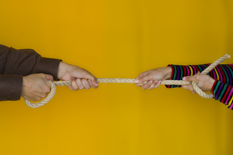 Contested divorce concept, man and woman stretching a rope on yellow background.