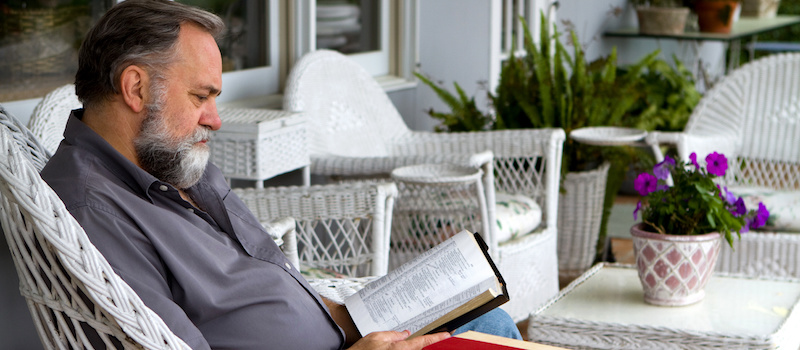 Old man holding a book while sitting in a white wicker chair outside.
