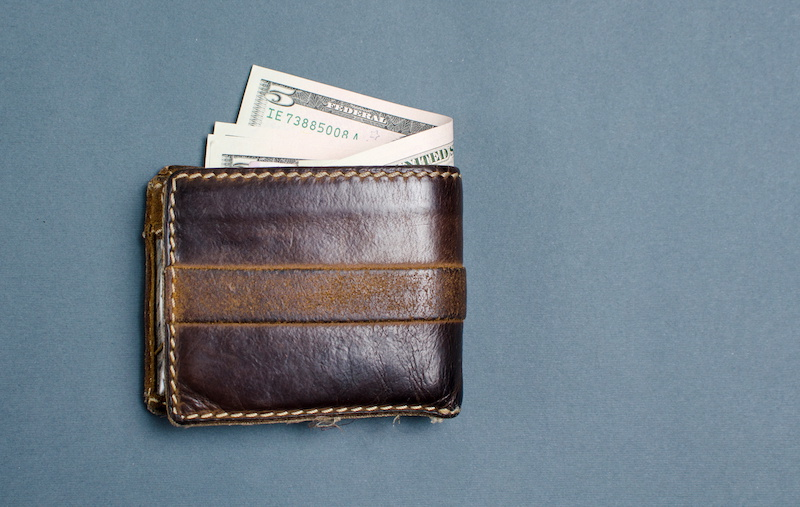 Dollar bills in a brown leather wallet