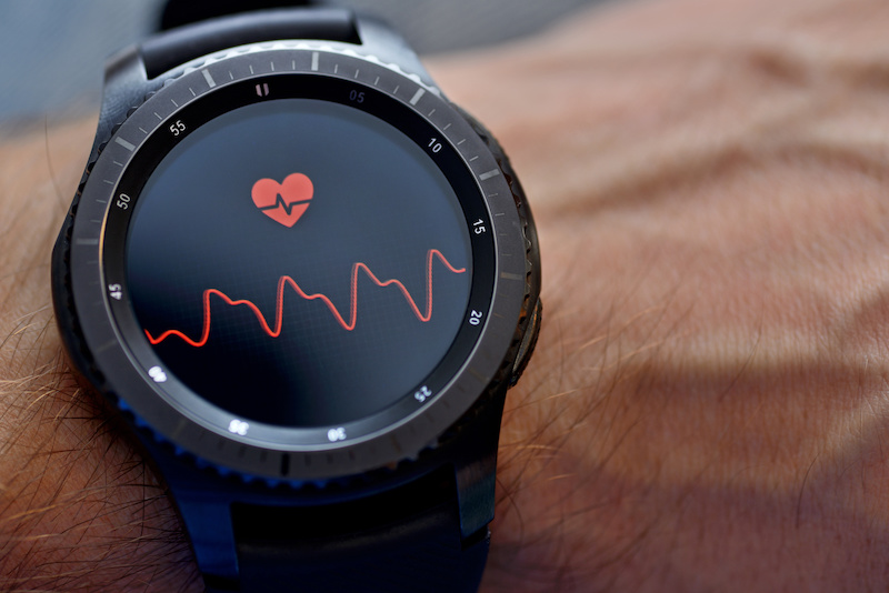 Smartwatch on a man's wrist, heart on face.