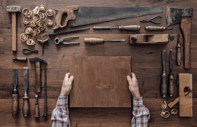 Carpenter holding a wood block and collection of vintage woodworking tools on a workbench.