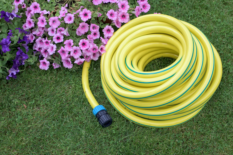 Yellow hose pipe on grass in a garden