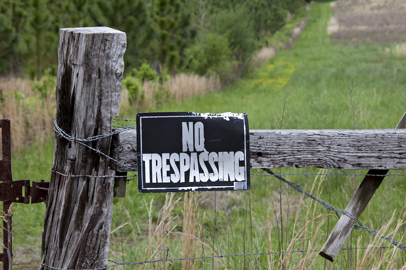 Warning sign for no trespassing on an old, weathered fence post with barbed wire at the entrance of a green meadow.