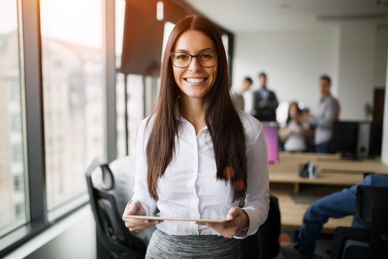 Portrait of beautiful young businesswoman holding tablet in office