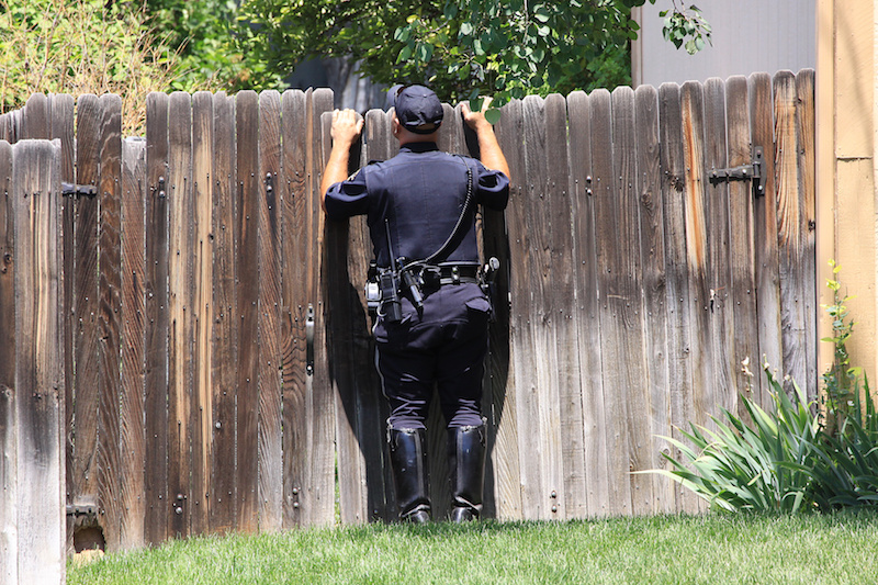 policeman looking over fence