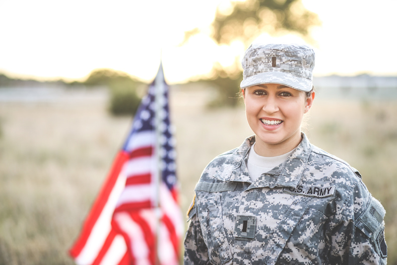 Army woman in uniform with the U.S. flag.