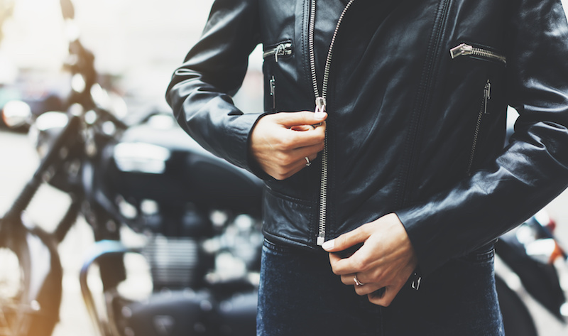 Woman in leather jacket standing in front of motorcycle.