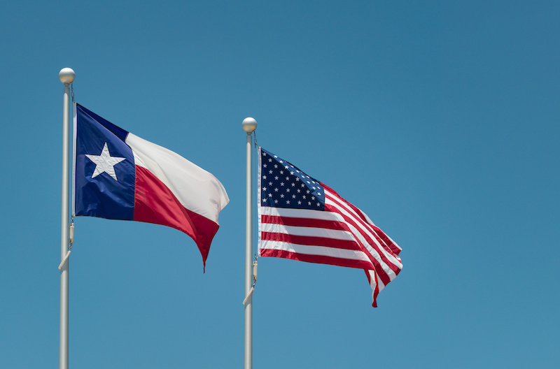 The state flag of Texas and American flag waving in the wind on flagpole. Blue sky background with copy space.