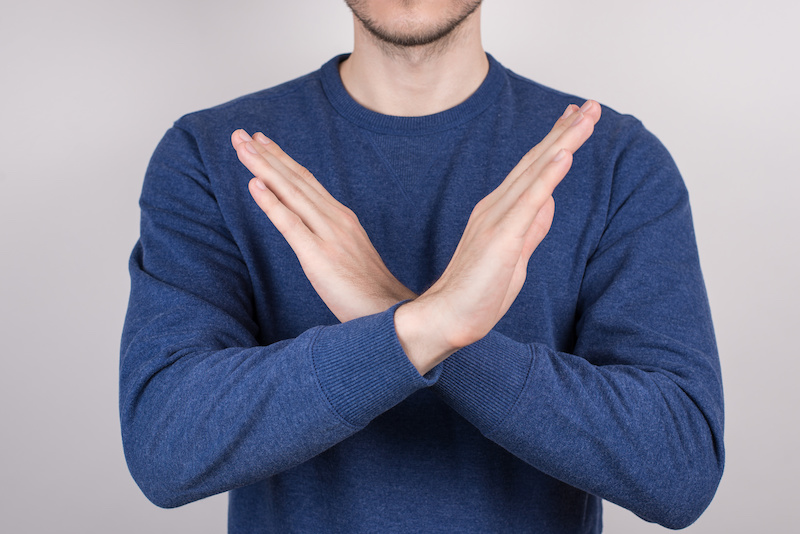 Close-up cropped photo portrait of confident handsome guy making demonstrating two crossed hands isolated grey background