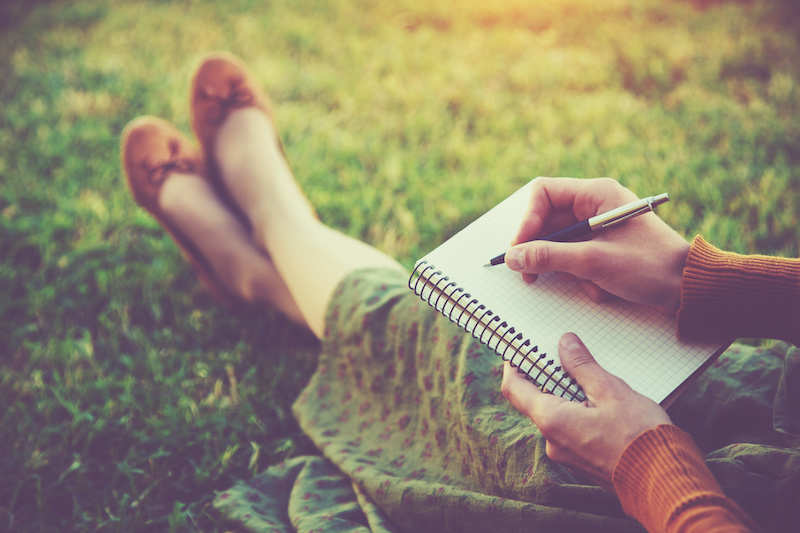 Woman writing in journal while sitting outside.