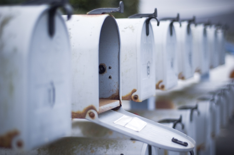 Open white mailbox in a row.