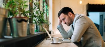 Worried man looking at laptop screen while sitting at modern cafe.