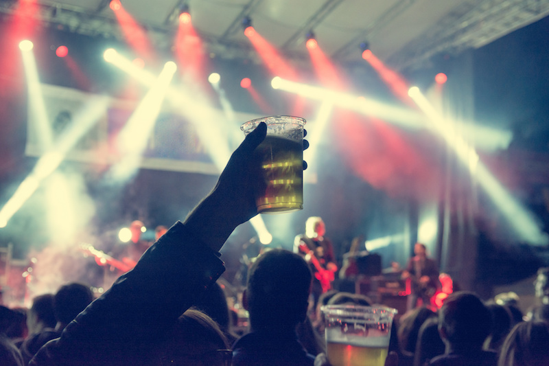 Raised beer glass at a concert. Consuming alcohol at music event.