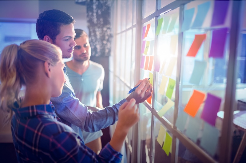 Young creative business people putting sticky notes on window.
