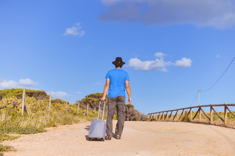 Back view of man walking with suitcase on blue sky outdoors background. Arriving at destination