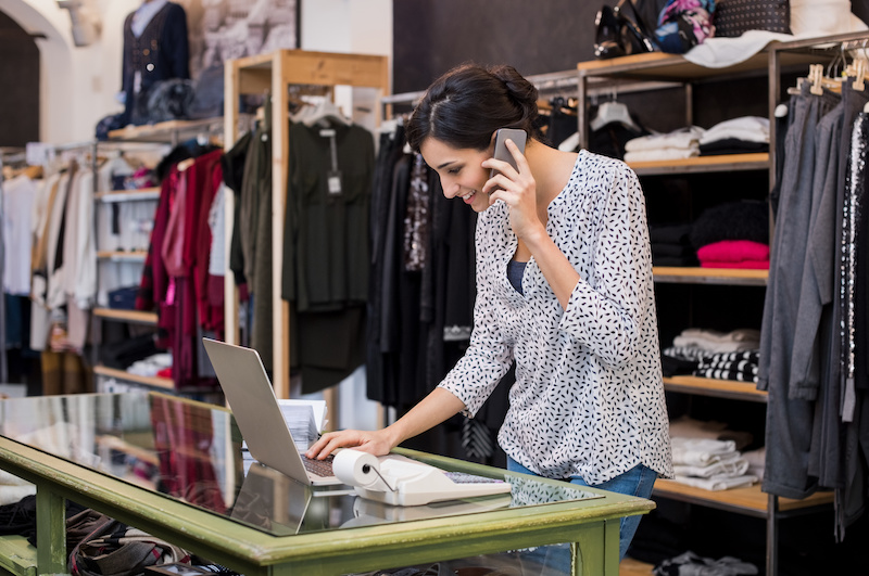 Young businesswoman talking over phone while checking laptop in her clothing store.