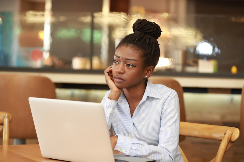 Young beautiful African girl sitting at table with laptop leaning on hand and thinking.