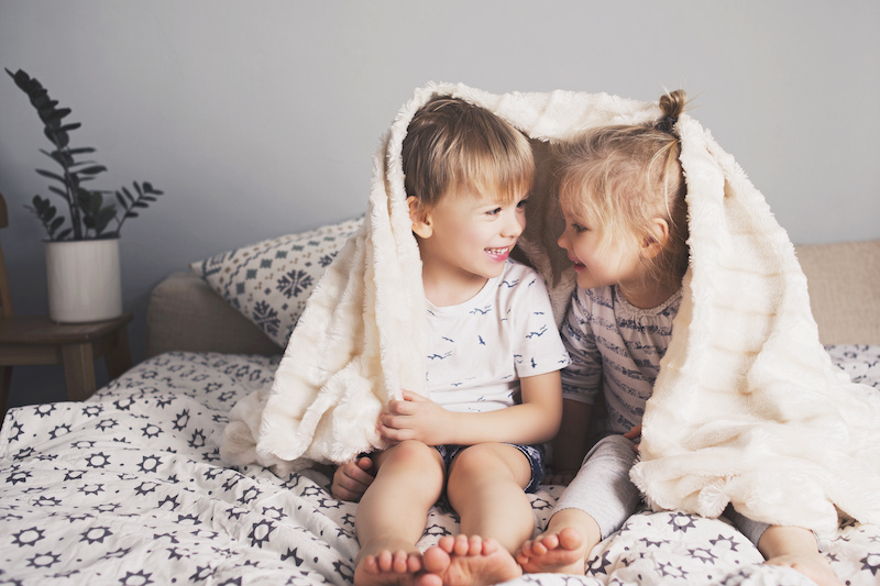 Two pretty smiling kids embrace under blanket