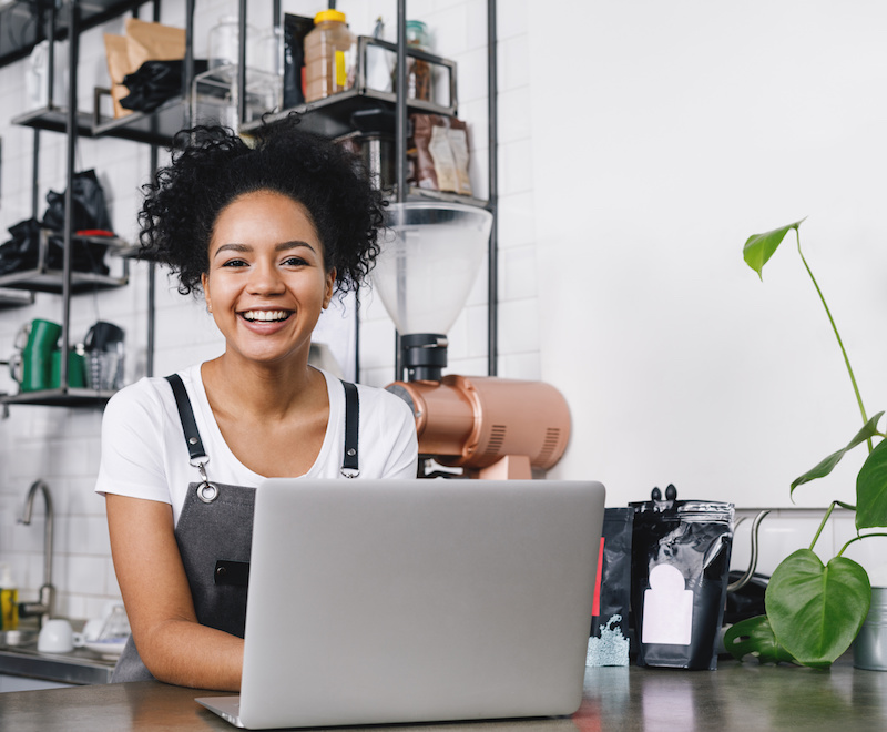 Happy business owner standing at counter with her laptop