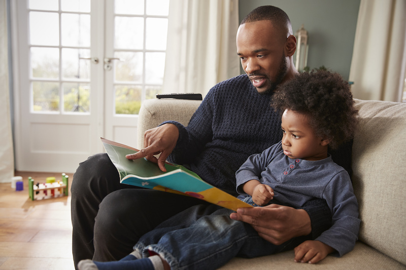 Father And Young Son Reading Book Together At Home