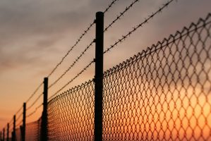 Chainlink fence with sunset in background.