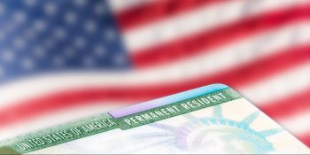 United States of America permanent resident cards, green card, with US flag in the background.