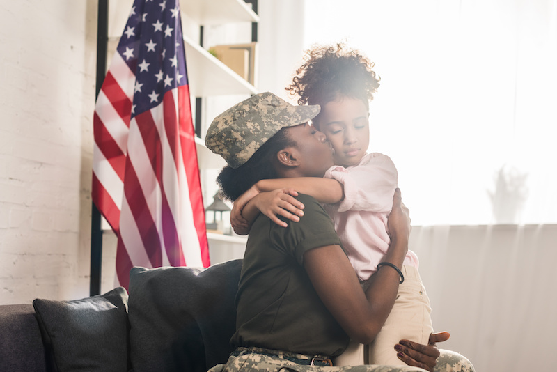 Woman in camouflage clothes kissing her daughter