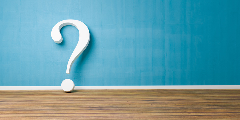 White question mark on blue concrete wall - FAQ Concept.