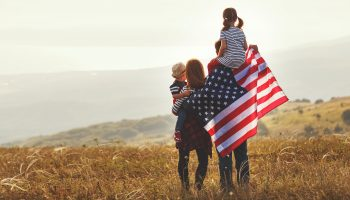 Happy family with US flag at sunset outdoors.
