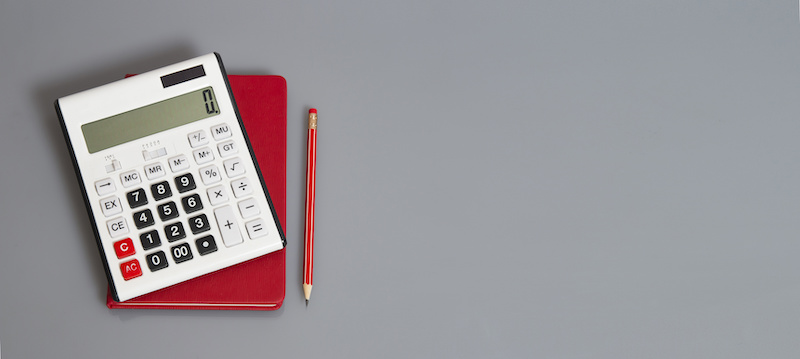 White calculator and red organizer on a grey table with red pencil
