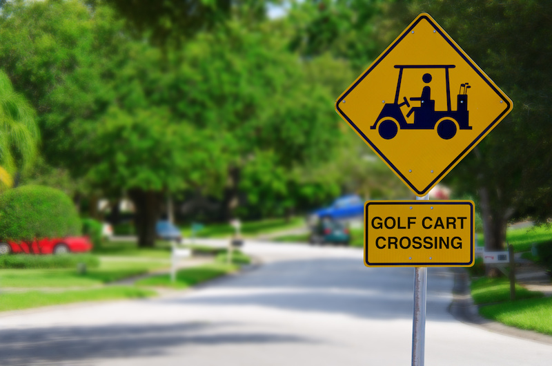 Golf Cart Crossing sign on a residential street intersection with blurred lush green trees in the background.