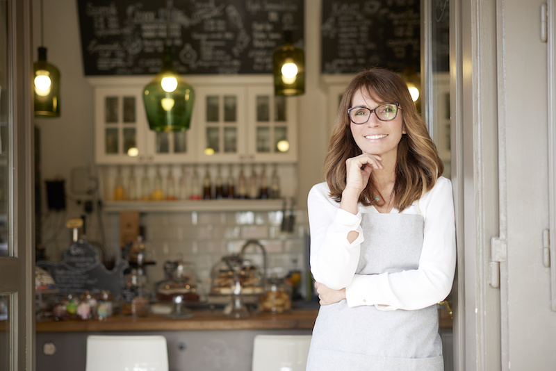 Shot of an attractive laughing woman standing in the doorway of a cafe. Small business.