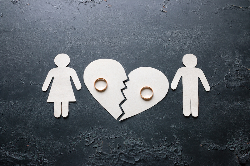 Paper family divided by a paper broken heart.