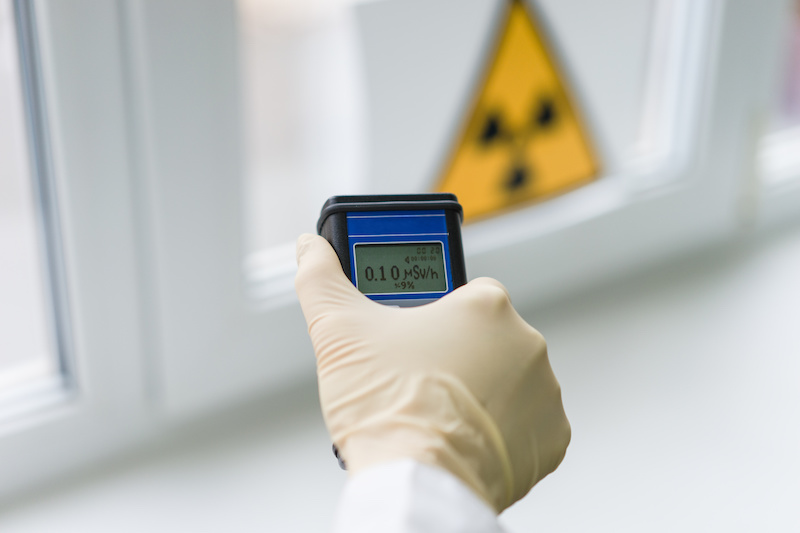 the scientist measures the level of radiation against the background of the sign of radiation hazard with the help of a dosimeter