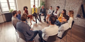 Business people talking at group meeting in circle