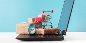 E-commerce sale and delivery service concept: shopping cart multicolored packages and boxes with trolleybus logo on laptop keyboard, blue background