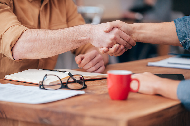 Sealing a deal. Close-up of two men shaking hands while sitting at the wooden desk