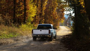 White pickup truck driving down dusty dirt road with fall leaves and dust behind