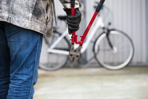 Man with bolt cutters walking towards a chained bike.