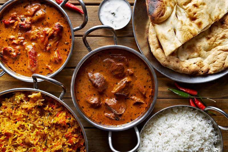 Assorted spicy food - indian curry and rice dishes shot from overhead.