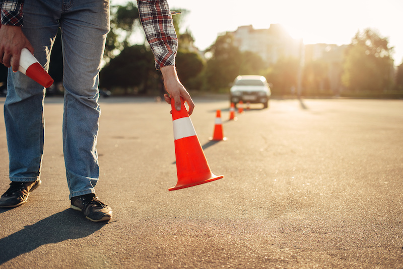 Instructor setting up cones for a driving lesson, driving school concept.