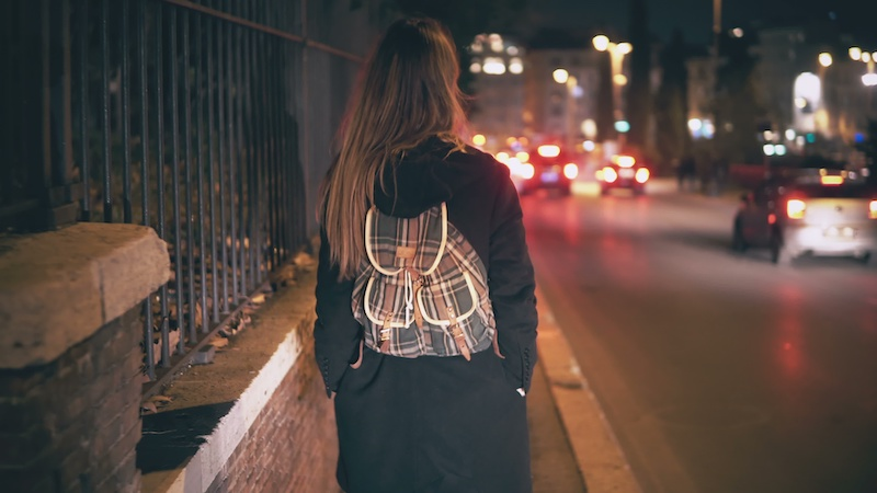 Brunette woman with backpack walking late at night.