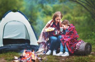 Family mother and child daughter drinking tea on a camping trip with a tent and by the bonfire