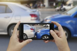 Close up hand holding smartphone and taking photos of a car accident. Collecting evidence.