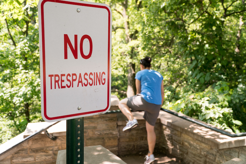 Young woman attempt to jump over railing into restricted area labelled by no trespassing sign.