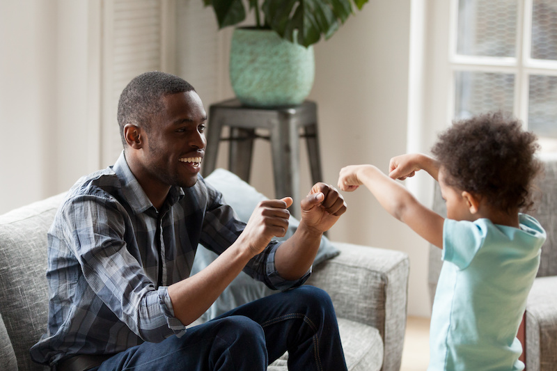 Adoption Concept - Father and son playing in a living room.