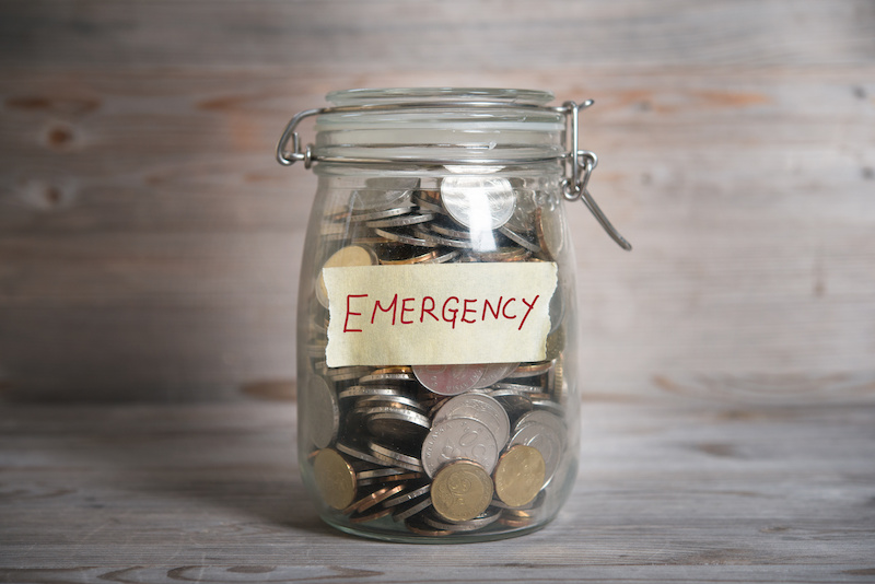 Coins in glass money jar with emergency label, financial concept. Vintage wooden background with dramatic light.